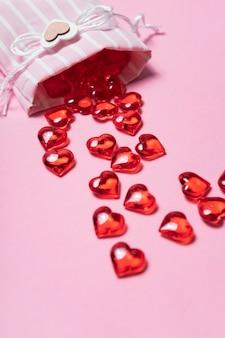 Selektiver fokus. valentinstagskarte. glasrote herzen aus einer schönen stofftasche verstreut. der blick von oben. rosa hintergrund