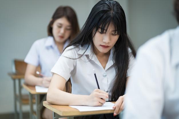 Selektiver fokus von college-studenten im teenageralter sitzt auf dem lehrstuhl, schreibt auf dem prüfungspapier antwortbogen und nimmt den abschlussprüfungsraum oder das klassenzimmer auf. universitätsstudenten in uniform im klassenzimmer.