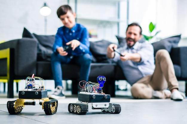 Selektiver fokus von robotern auf dem boden, während vater und sohn sie mit fernbedienungen testen