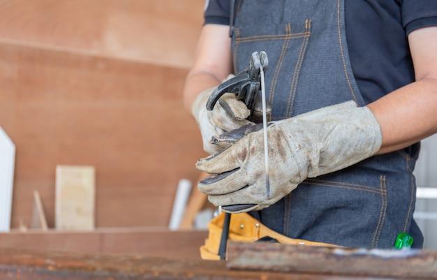 Selektiver fokus von schweißelektrodenhaltern mit schweißdraht in der arbeitskrafthand, handwerkerkonzept