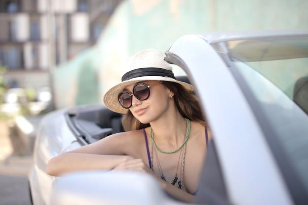 Selektiver fokusschuss der frau auf dem fahrersitz eines weißen cabrio-sportwagens