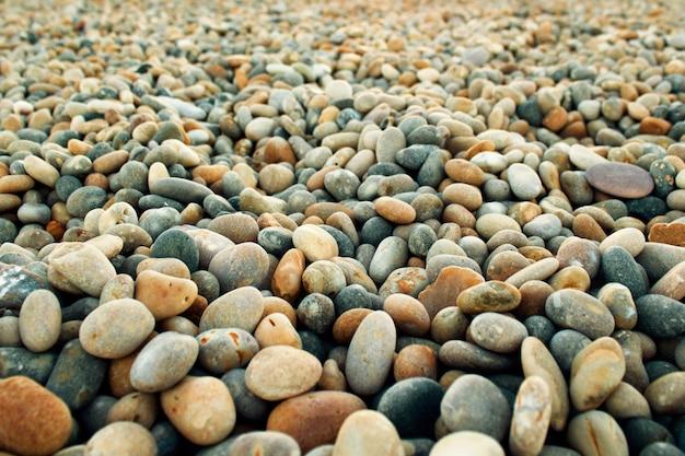 Selektiver fokusschuss der nahaufnahme von runden kleinen kieselsteinen am strand