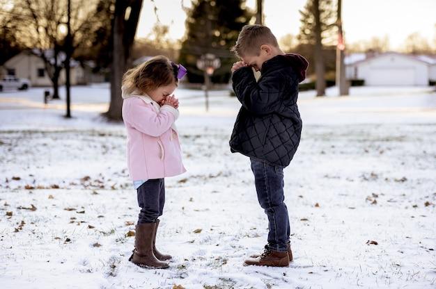 Selektiver fokusschuss der niedlichen kleinen kinder, die mitten in einem winterpark beten