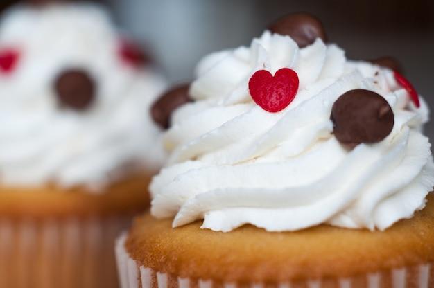 Selektiver fokusschuss des weißen zuckergusses auf einem cupcake mit schokoladenstückchen