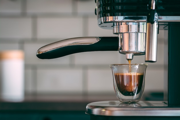 Selektiver fokusschuss einer espressomaschine, die am morgen leckeren warmen kaffee macht