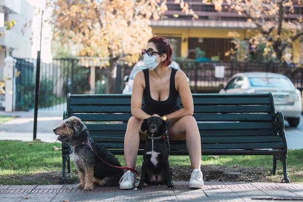 Selektiver fokusschuss einer frau in einer maske, die auf einer bank mit hunden sitzt