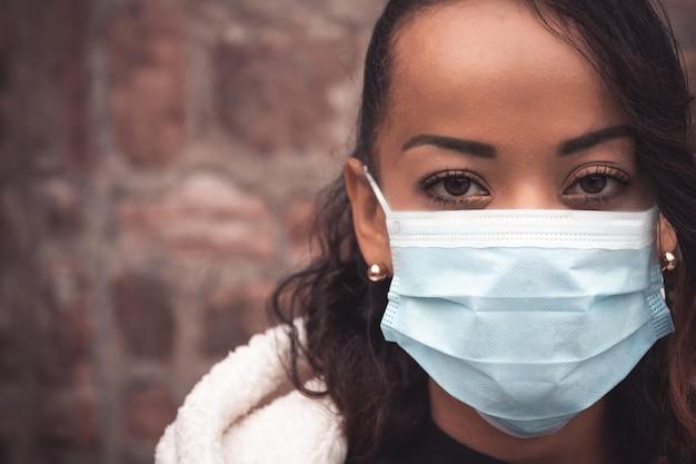 Selektiver fokusschuss einer jungen frau, die eine medizinische maske trägt - bleiben sie sicheres konzept