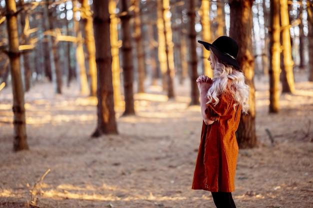 Selektiver fokusschuss einer schönen jungen dame, die in einem wald betet