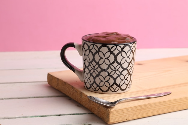 Selektiver fokusschuss einer tasse heißer schokolade auf einem holzbrett mit einem rosa hintergrund