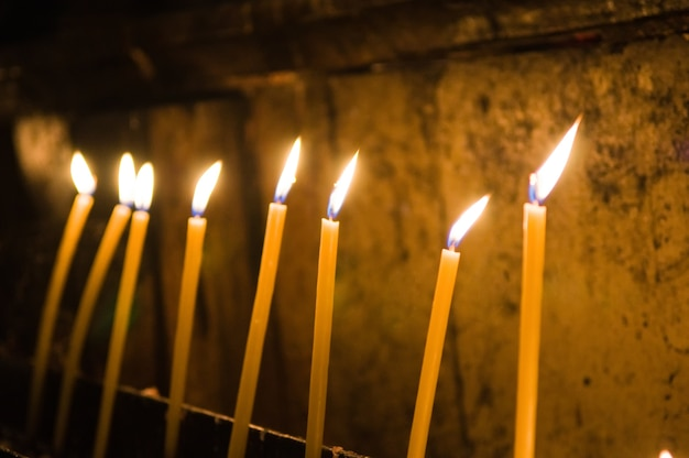 Selektiver fokusschuss von brennenden gelben kerzen innerhalb der kirche