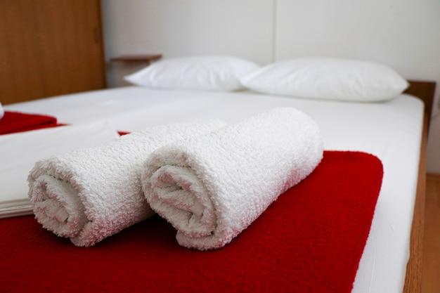 Selektiver fokusschuss von gerollten handtüchern, die auf einem ordentlichen weißen bett mit einem unscharfen hintergrund angeordnet sind
