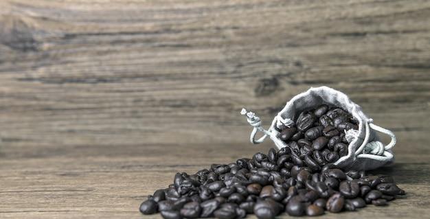 Selektiver fokusschuss von kaffeebohnen, die den beutel auf einer holzoberfläche verschütten