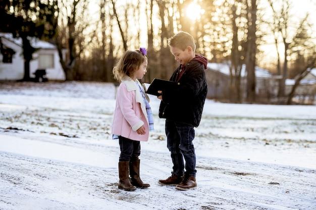 Selektiver fokusschuss von niedlichen kleinen kindern, die die bibel mitten in einem winterpark lesen