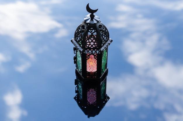 Selektiver laternenfokus mit reflexion verschwommener hintergrund von wolken und himmel für das islamische neujahrskonzept