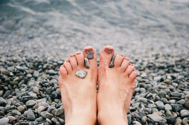Selektiver nahaufnahmeschuss von kieselsteinen auf den beinen einer kaukasischen person