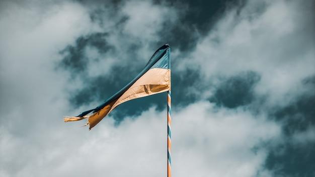 Selektiver schuss der gelben und blauen flagge der ukraine auf fahnenmast auf dem hintergrund eines bewölkten himmels