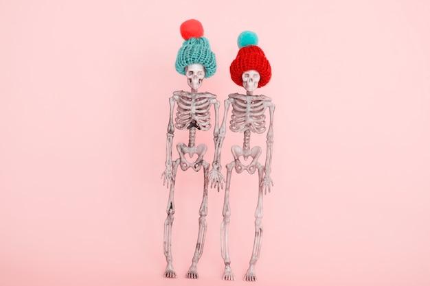 Selektives fokuspaar skelette, die niedliche strickmütze auf einem rosa hintergrund tragen