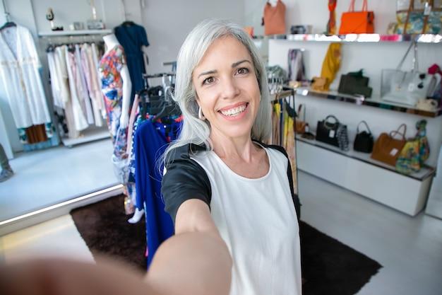 Selfie der fröhlichen kaukasischen blonden frau, die nahe gestell mit kleidern im modegeschäft steht, kamera betrachtet und lächelt. boutique-kunden- oder verkäufer-konzept