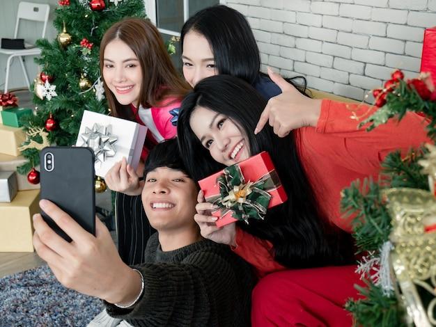 Selfie der gruppe junger asiaten mit geschenken zu hause beim feiern des weihnachtsfestes. gruppe von freunden, die sich zusammen für die weihnachtsfeier verkleiden. feiern des neuen jahres. frohe weihnachten und schöne feiertage.
