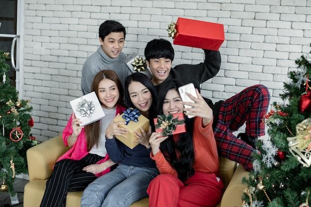 Selfie der gruppe junger asiatischer mit geschenken zu hause beim feiern des weihnachtsfestes