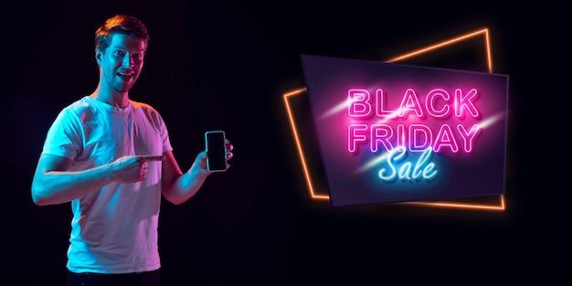 Selfie, erstaunt. porträt des jungen mannes in neon auf dunklem studiohintergrund. menschliche emotionen, schwarzer freitag, cyber-montag, einkäufe, verkäufe, finanzkonzept. exemplar. nahtloser beitrag für instagram.