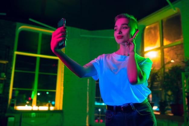 Selfie. filmporträt der stilvollen frau im neonbeleuchteten innenraum. getönt wie kinoeffekte, leuchtende neonfarben. kaukasisches modell mit smartphone in bunten lichtern drinnen. jugendkultur.