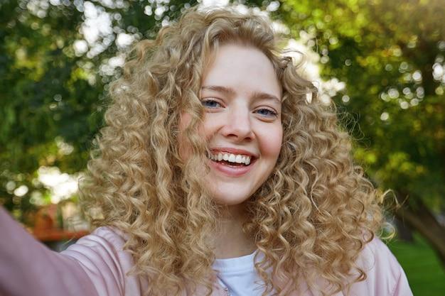 Selfie foto der jungen schönen schönen frau blondine mit lockigem haar