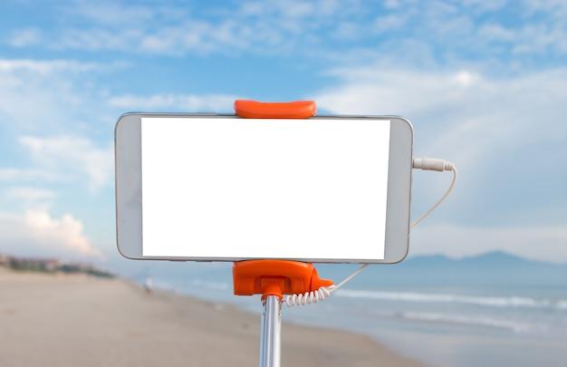 Selfie-fotokonzept: spott herauf ausdehnbaren selfie stock oder einbeinstativ mit dem handy, der foto macht