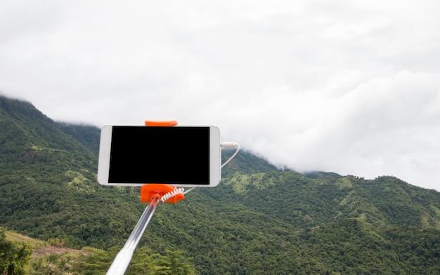 Selfie-fotokonzept: spott herauf ausdehnbaren selfie stock oder einbeinstativ mit mobile