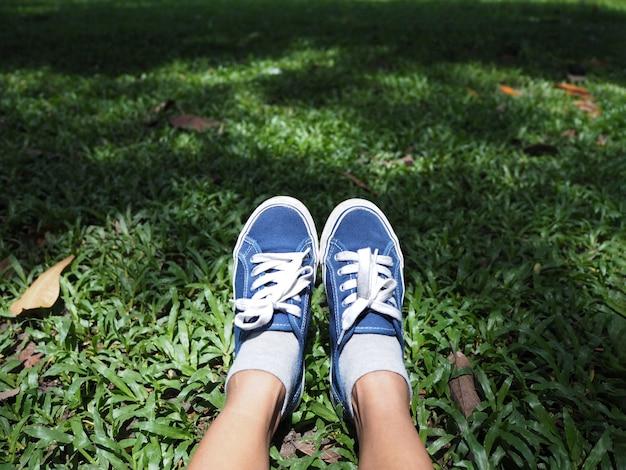 Selfie-füße, die blauen turnschuh auf grünem gras im park tragen.