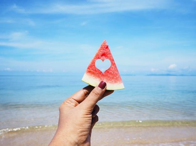 Selfie-hand, die wassermelone über sommerstrand hält
