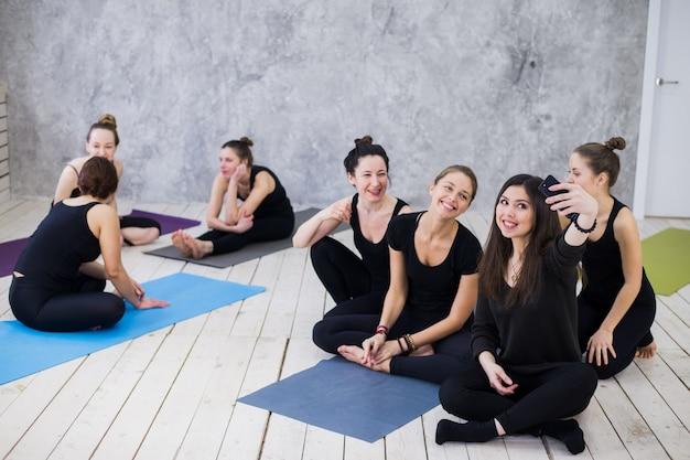 Selfie machen. gruppe von mädchen in der fitnessklasse in der pause, die handy, glücklich und lächelnd betrachten, zeigen lustiges gesicht. frauenfreundschaft, gesundes modernes leben des jugendkonzepts.
