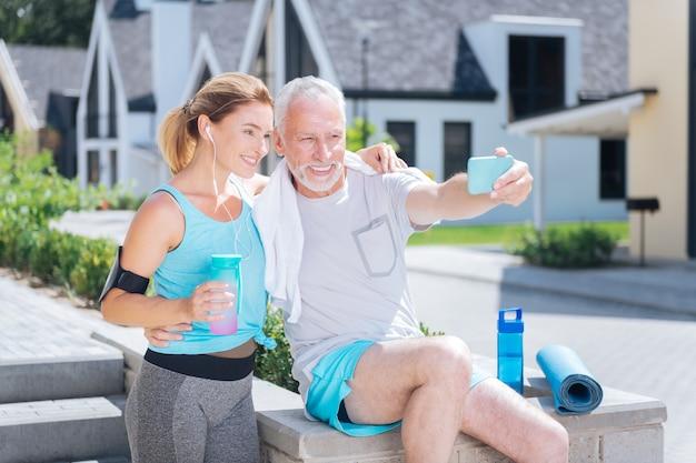 Selfie mit frau. bärtiger reifer mann, der sein blaues smartphone hält, während er selfie mit ansprechender blonder frau macht
