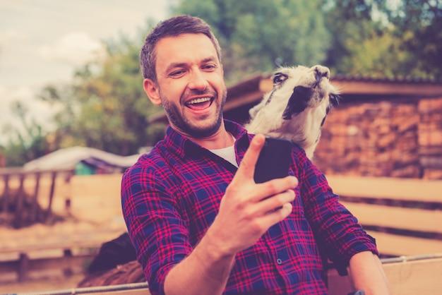 Selfie mit lama. fröhlicher junger mann macht selfie mit lama auf seinem smartphone, während er im zoo steht