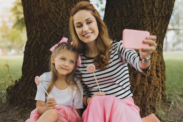 Selfie mit tochter. moderne liebende mutter, die denkwürdiges selfie mit niedlicher lustiger tochter macht