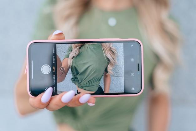 Selfie oder selfy-porträt schöne junge frau, die sich auf dem handy fotografiert