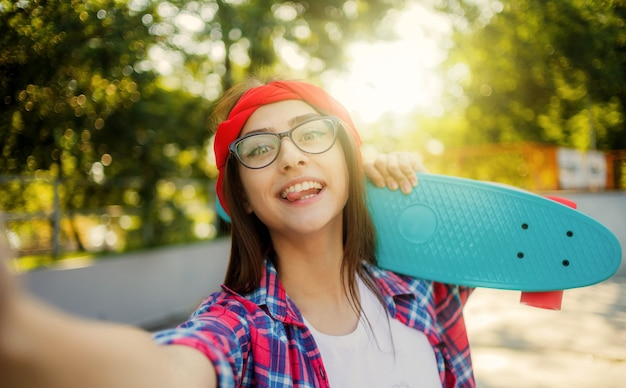 Selfie-porträt der lustigen jungen frau mit brille und rotem kariertem hemd. hipster-mädchen, die im skatepark herumalbern, während sie am sonnigen hellen tag mit skateboard im skatepark fotografieren.