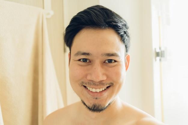 Selfie-porträt des glücklichen mannes im badezimmer.