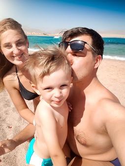 Selfie-porträt von eltern, die am sonnigen windigen tag den kleinen kleinkindsohn am strand küssen. familie, die sich während der sommerferien entspannt und gute zeit hat.