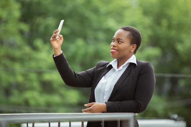 Selfie, videoanruf. afroamerikanische geschäftsfrau in bürokleidung lächelnd, sieht selbstbewusst und glücklich aus, beschäftigt. finanzen, wirtschaft, gleichstellung, menschenrechtskonzept. schönes junges weibliches modell, erfolgreich.