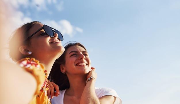 Selfie von zwei lächelnden mädchen im freien, die am sonnigen tag ein gutes wochenende zusammen haben.