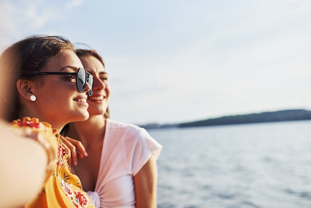 Selfie von zwei lächelnden mädchen im freien, die am sonnigen tag gegen den see ein gutes wochenende zusammen haben.