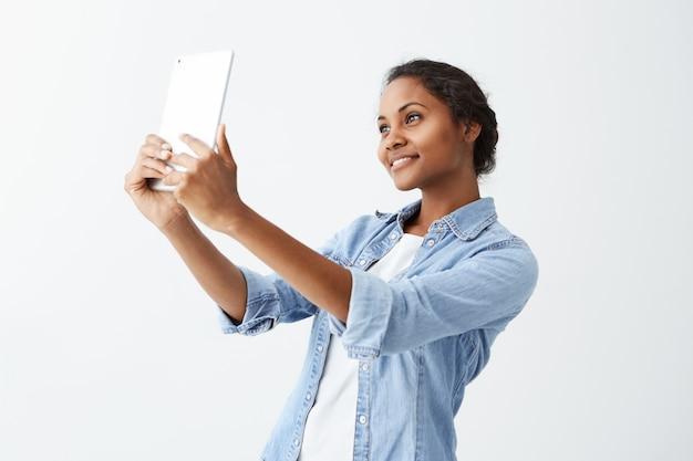Selfie zeit. freudige junge attraktive afroamerikanische frau mit dunklem haar im blauen hemd, das selfie macht, tablette in ihren händen haltend. dunkelhäutiges junges schönes mädchen, das für selfie auf weißer wand aufwirft