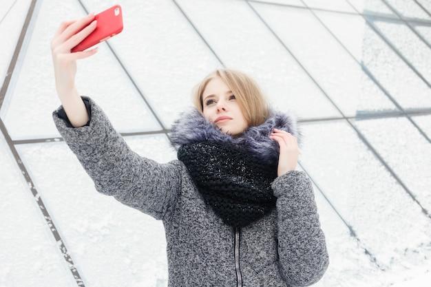 Selfie-zeit, junge funky bloggerin macht ein foto für ihre social-network-seite. junge glückliche frau, die selfie nimmt. kaltes sonniges wetter. frau winterkonzept.