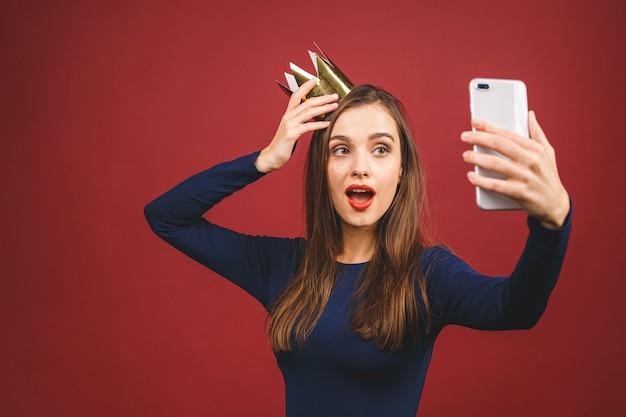 Selfie zeit! porträt mit leerem platz des copyspace der selbstbewussten stolzen arroganten jungen frau mit goldener krone auf ihrem kopf lokalisiert auf rotem hintergrund.