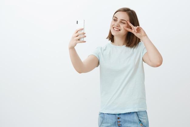 Selife-ähnliche methode des selbstausdrucks. freundlich aussehendes geselliges und freundliches europäisches mädchen mit kurzen braunen haaren, die friedenszeichen nahe gesicht lächelnd auf bildschirm zeigen, das foto von sich auf neuem smartphone macht