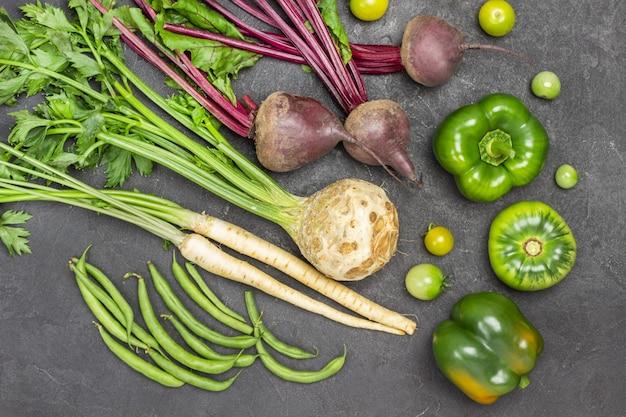 Sellerie, petersilie, rüben mit spitzen auf dem tisch. grüne paprika, grüne bohnen und grüne tomaten. flach liegen. schwarzer hintergrund