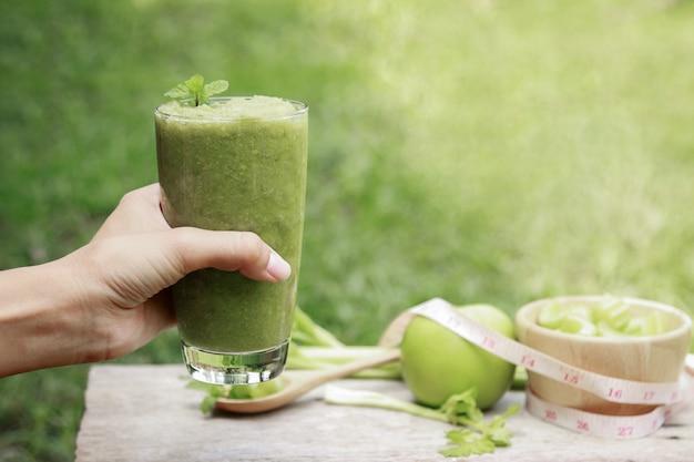 Selleriesaft im glas für die gesunde ernährung mit ballaststoffen mit handgriff