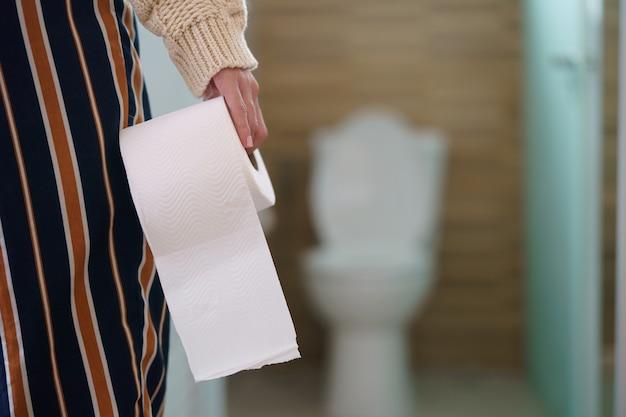 Seltene ansicht der frau, die toilettenpapierrolle in der vorderseite der toilette hält.