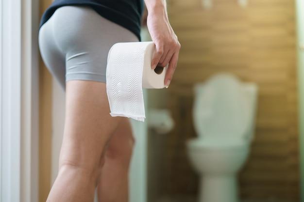 Seltene ansicht des mannes, der toilettenpapierrolle in der vorderseite der toilette hält.